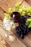 Vino rosso e vino bianco con l'uva ed i vetri su backgr rustico Fotografia Stock Libera da Diritti