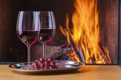 Vino rosso ed uva al camino Immagini Stock