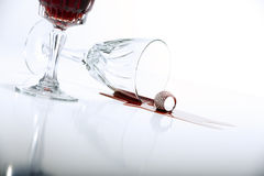 Vino rosso rovesciato dal bicchiere di vino a cristallo Fotografie Stock