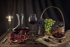 Vino rosso in un vetro, canestro con l'uva, melograno, candela su una tavola di legno immagini stock