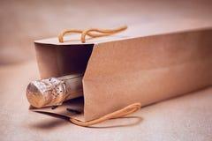 Vino spumante nella borsa del regalo del mestiere sul backgro astratto della carta del mestiere Immagine Stock Libera da Diritti