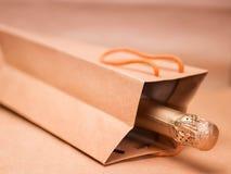 Vino spumante nella borsa del regalo del mestiere sul backgro astratto della carta del mestiere Fotografia Stock