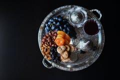 Vino tinto, copa con las nueces, uvas e higos en fondo de madera oscuro fotografía de archivo