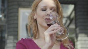 Vino tinto de consumici?n de la mujer elegante del retrato del alto vidrio en el cierre del aire libre del caf? para arriba Se?or almacen de metraje de vídeo