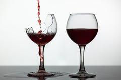 Vino tinto que vierte en la copa de vino quebrada en la superficie mojada El vino rosado Vierte fotografía de archivo libre de regalías