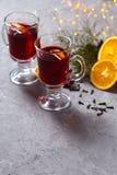 Vino tinto reflexionado sobre con las especias y la naranja en fondo oscuro Bebida que se calienta imágenes de archivo libres de regalías