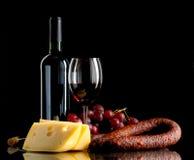Vino, uvas, queso y salchicha en fondo negro Foto de archivo