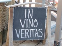 In vino veritas sign. In vino veritas blackboard sign, wood framed outside a store Stock Photography