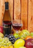 Vino y frutas en fondo de la pared de madera Foto de archivo