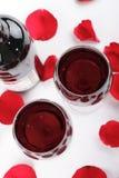 Vino y pétalos color de rosa Imagen de archivo libre de regalías