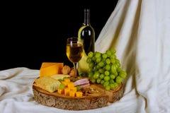 Vino y variedad de queso en aún-vida de madera de la tabla Fotografía de archivo