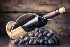 Vinodlingbakgrund Flaska av rött vin med klungan av mörker - blåa druvor på trätabellen Royaltyfria Bilder