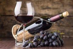 Vinodlingbakgrund Vinglas med flaskan av rött vin och klungan av druvan Royaltyfria Foton