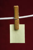 Vinous. Yellow paper attach clothes-peg to rope on vinous background Stock Photography