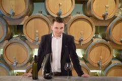 Vinproducent som kontrollerar kvalitet av rött vin som står nära flaskkuggar i vinodlingvalv Royaltyfria Bilder