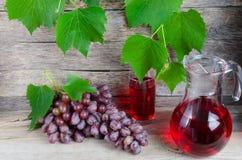 Vinrankakaraff och ett exponeringsglas av druvafruktsaft Arkivbild