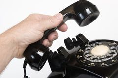 Vintage 1960s telephone. Picking up the receiver on a vintage 1960s telephone Royalty Free Stock Photo