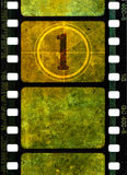 Vintage 35mm movie film reel. Vintage 35mm film reel, colorful grunge textured film frames and a number one in countdown Stock Images
