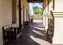 Exterior arched walkway at a mission in California. Vintage adobe arched walkway with wooden benches outside Santa Ines mission in California with early morning Royalty Free Stock Images