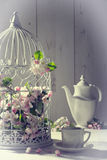 Vintage Afternoon Tea. With birdcage filled with spring blossom Royalty Free Stock Photos