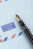 Vintage airmail envelope and fountain pen. Vintage airmail envelope with a letter and fountain pen Stock Photography