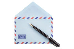 Vintage airmail envelope and fountain pen. Vintage airmail envelope with a letter and fountain pen over white Royalty Free Stock Photography