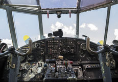 Vintage airplane cockpit. Interior with blue sky and white clouds in the background Royalty Free Stock Photo