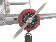 Vintage airplane engine, propeller, and wing isola. Radial engine, red cowling, and propeller on a vintage airplane showing part of the silver fuselage, wing and stock photo