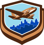 Vintage Airplane Take Off Cityscape Shield Retro. Illustration of a vintage passenger DC10 airplane take off with cityscape buildings in background set inside Stock Photos