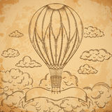 Vintage airship with ribbon and clouds on aged paper background. Stock Images