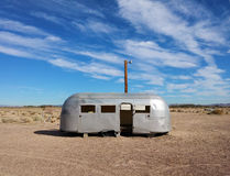 Vintage airstream trailer. Forgotten vintage airstream trailer and retro electricity pylon with blue sky, summer middle of nowhere, Newberry Springs, California stock photo