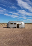 Vintage airstream trailer. Forgotten vintage airstream trailer and retro electricity pylon with blue sky, summer middle of nowhere, Newberry Springs, California Royalty Free Stock Photo