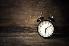 Vintage Alarm black clock. Vintage black clock on wooden wall desk Royalty Free Stock Images
