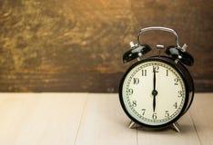 Vintage Alarm black clock. Vintage black clock on wooden wall desk Stock Photo