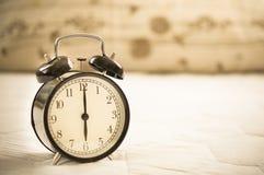Vintage Alarm black clock. Vintage black clock on wooden wall desk Royalty Free Stock Photo