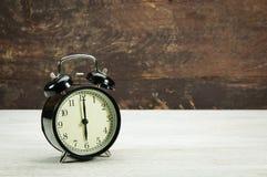Vintage Alarm black clock. Vintage black clock on wooden wall desk Stock Images