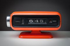 Vintage alarm clock. Vintage orange alarm clock on a dark background Stock Image