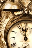 Vintage alarm-clock. Detail of antique alarm-clock with old christmas baubles in sepia tone Stock Photo
