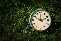 Vintage alarm clock on a background of green grass. Copy space. Time concept, business planning stock photography