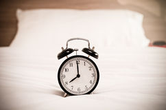 Vintage alarm clock on the bed Stock Photos
