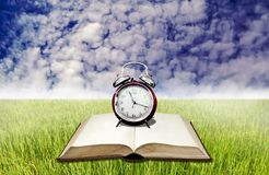 Vintage alarm clock on blank book on rice field. With blue sky royalty free illustration