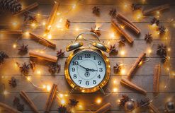 Alarm clock and cinnamon, star anise with Christmas lights. Vintage alarm clock and cinnamon, star anise with Christmas lights around on wooden background Royalty Free Stock Image