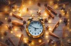 Alarm clock and cinnamon, star anise with Christmas lights Royalty Free Stock Image