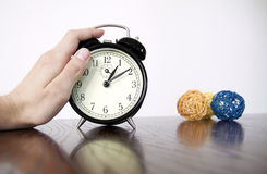 Vintage alarm clock closeup with hand. Vintage alarm clock closeup with man hand royalty free stock photography