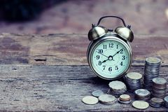 Vintage alarm clock and coin stacks on wooden table with blur green garden background, bright morning color tone, finance and stock images