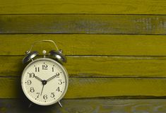 A vintage alarm clock on a colored wooden table. Top view.  Royalty Free Stock Images