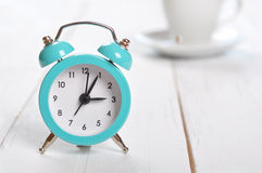 Vintage alarm clock. With cup of coffee on white background Royalty Free Stock Images