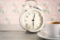 Vintage alarm clock with cup of coffee Royalty Free Stock Photos