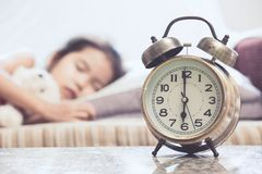 Vintage alarm clock on cute asian child girl sleeping in the bed Royalty Free Stock Photos