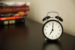 Vintage alarm clock on dark brown surface. Shows 7 o'clock. Pile Royalty Free Stock Image